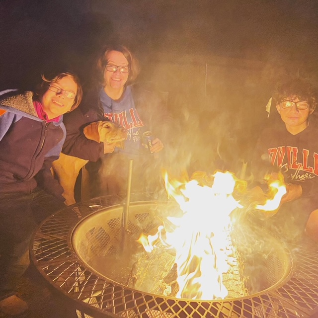 Picture of people sitting around the campfire as part of this fire pit review, best fire pit,